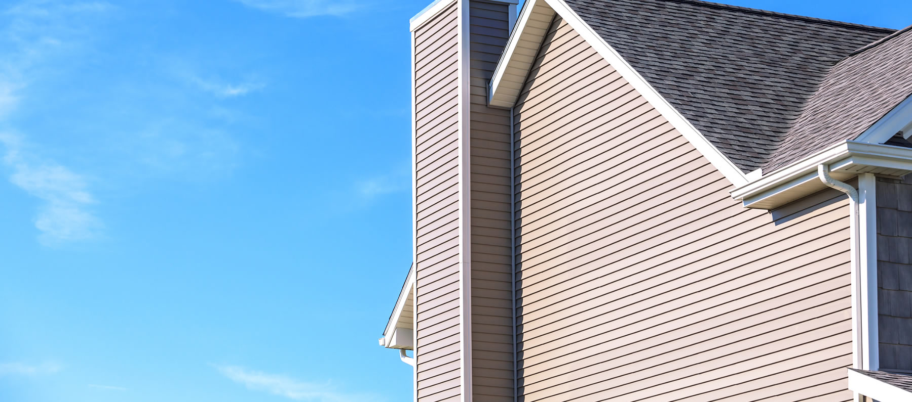 Blue sky with a tan colored home showing the siding